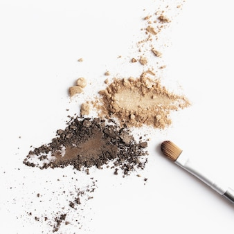 Ombretto e ombretto o pennello per il trucco sparsi di colore marrone chiaro e scuro