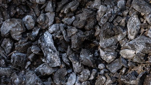 Pezzi di brace sparsi nel focolare mescolati con cenere sfondo di bricchette di carbone nero caldo
