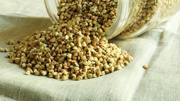 Grano saraceno verde crudo sparso con un barattolo di vetro per i cereali concetto di cibo biologico vegano. il concetto di dieta, perdita di peso, alimentazione sana e corretta. noccioli sparsi a forma di triangolo.