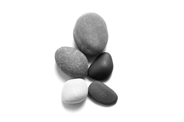 Ciottoli di mare sparsi. pietre lisce grigie e nere isolate su priorità bassa bianca. vista dall'alto