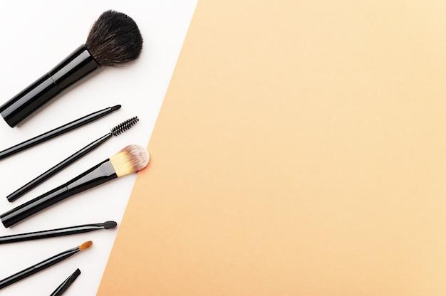 Strumenti visagiste sparsi per l'applicazione di cipria, fondotinta per viso, ombretto
