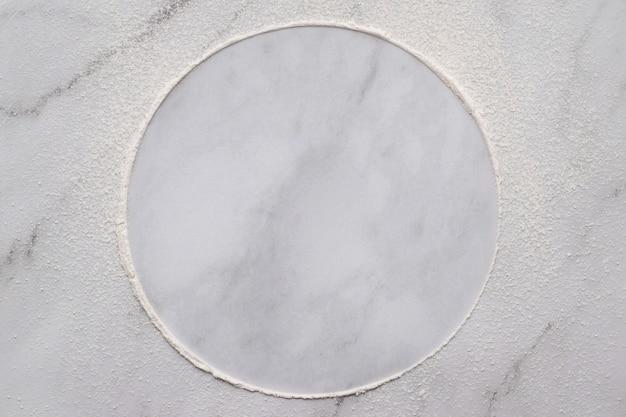Farina di frumento sparsa su fondo di marmo bianco. cerchio di farina di frumento cosparso su priorità bassa bianca.
