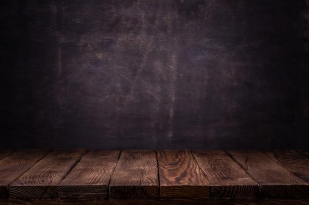 Creatore di scene. tabella vuota ponte di legno con sfondo scuro muro di cemento.