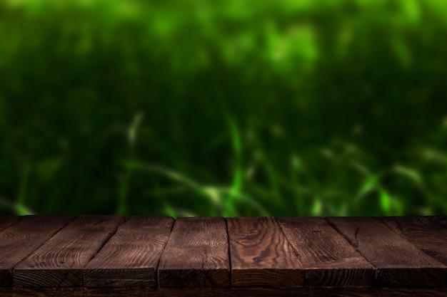 Creatore di scene. tavola di legno vuota della piattaforma con il fondo del bokeh di estate.