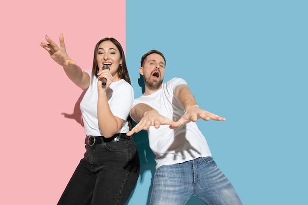 Scena. ballare, cantare, divertirsi. giovane e felice uomo e donna in abiti casual sulla parete bicolore rosa, blu. concetto di emozioni umane, espressione facciale, relazioni, pubblicità. bella coppia.