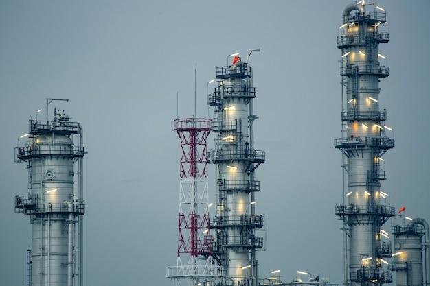 Serata di scena della torre dell'impianto di raffineria di petrolio del serbatoio e della conduttura del fumo della distilleria della colonna