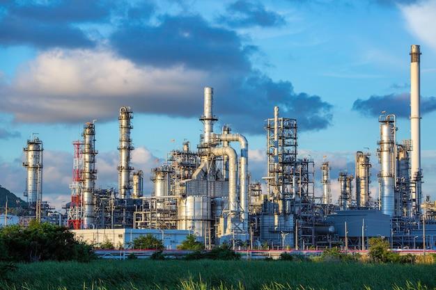 Serata di scena della torre dell'impianto di raffineria di petrolio del serbatoio e dell'olio del serbatoio della colonna dell'industria petrolchimica cielo blu e prato