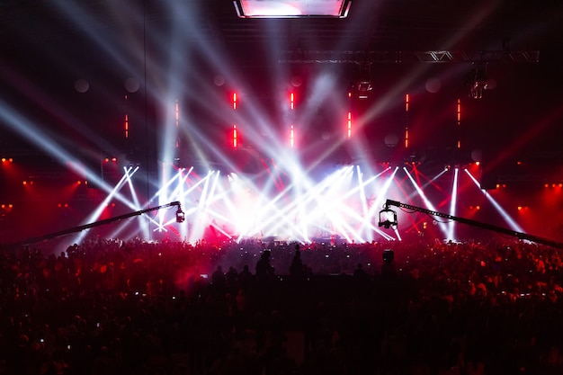 Scena illuminata da bellissimi raggi di apparecchi di illuminazione. la folla del concerto si diverte al centro nella grande sala.