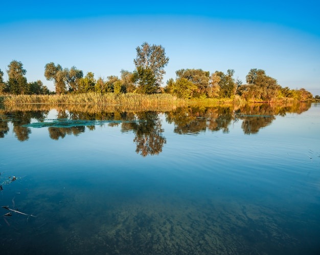 Scenario del grande lago tranquillo con acqua fresca in giornata estiva e campagna