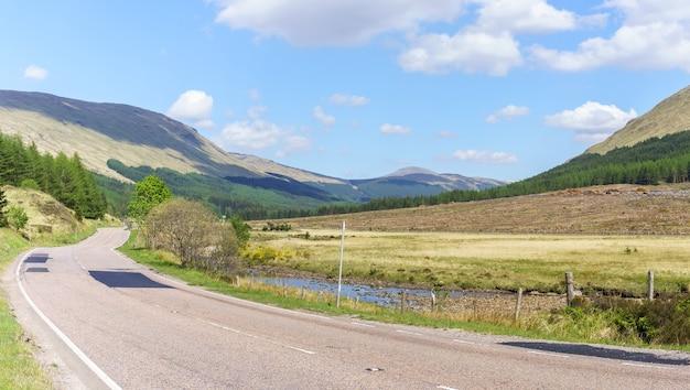 Scenario dei classici viaggi nelle highlands sulla strada principale in scozia con cielo blu in estate