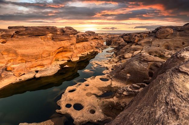 Scenario di eroso grandi rapide rocciose gola con fiume mekong e cielo colorato al tramonto a sam phan bok