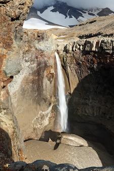 Paesaggio paesaggistico della cascata della penisola di kamchatka sul fiume di montagna sotto il vulcano attivo