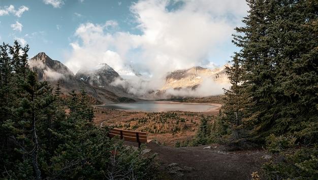 Scenario del monte assiniboine con il lago magog nella foresta di autunno e panca in legno