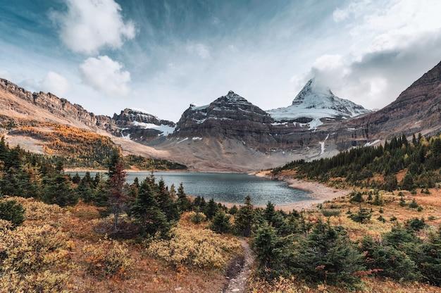 Scenario del monte assiniboine con il lago magog nella foresta di autunno