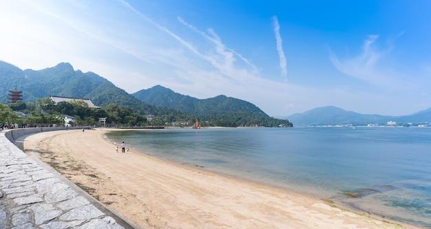 Paesaggio della costa del mare sull'isola di miyajima che osserva il famoso cancello shintoista giapponese galleggiante arancione (torii) del santuario di itsukushima nella baia