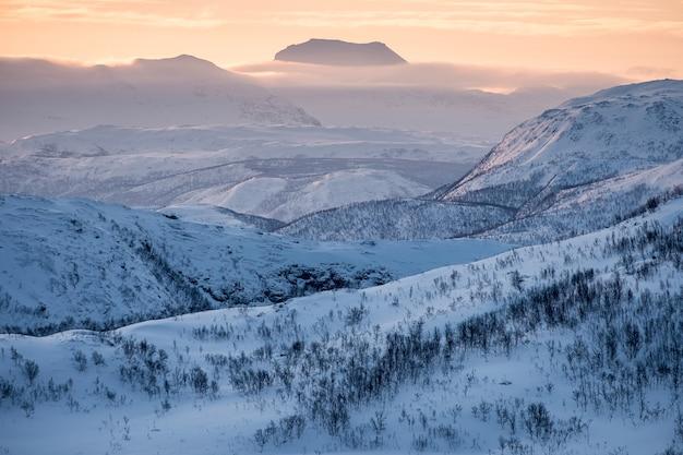 Paesaggio catena montuosa innevata con cielo colorato sul picco all'alba