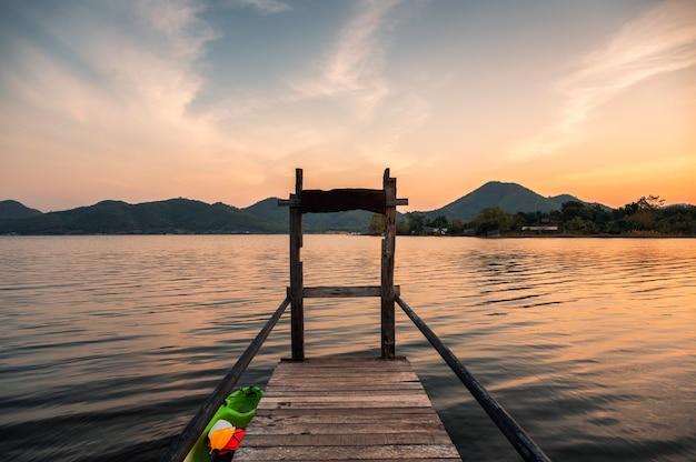 Scenario dell'alba sulla catena montuosa e sul molo di legno nel bacino idrico di lam thaphoen a suphanburi