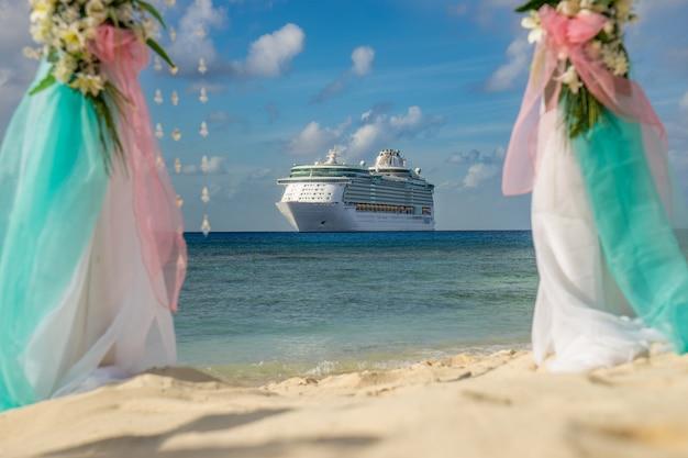 Scenario per un matrimonio sulla spiaggia con una nave da crociera sullo sfondo.