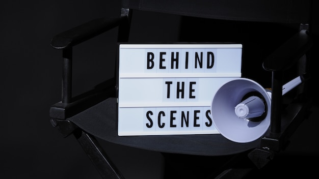 Testo della lavagna dietro le quinte su lightbox e megafono sulla sedia del regista