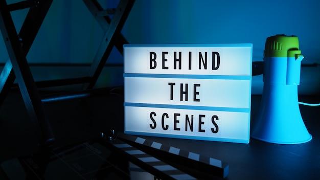 Scatola luminosa dietro le quinte. testo sulla scatola luminosa del cinema. megafono e sedia da regista e ardesia di film accanto. dietro il concetto di scena.