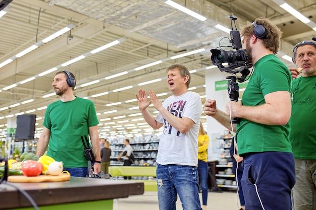 Dietro le quinte delle riprese di un film o della produzione video e della troupe cinematografica con attrezzatura fotografica in un luogo all'aperto.