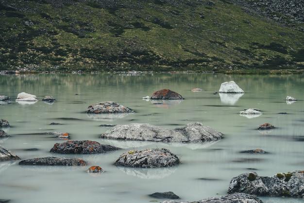 Paesaggio alpino panoramico con cerchi piovosi tra pietre con muschi e licheni nella superficie dell'acqua verde del lago di montagna paludoso. scenario atmosferico con cerchi di pioggia nel lago di montagna impregnato d'acqua.