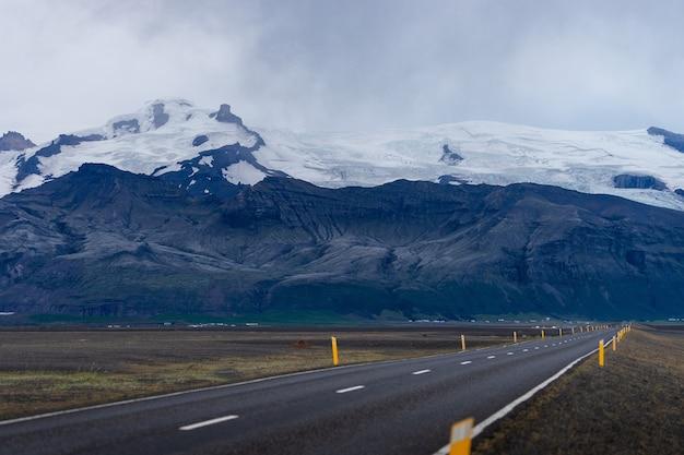Paesaggio panoramico con bella strada, montagna con ghiacciaio e picco innevato.
