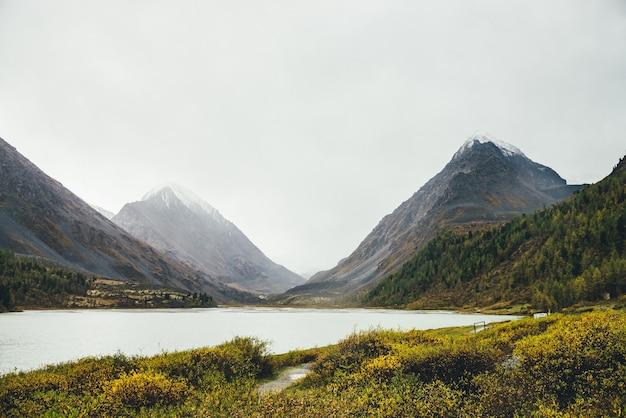 Paesaggio panoramico con lago di montagna nella valle d'oro autunnale tra rocce con neve nella nebbia. paesaggio alpino colorato con valle d'oro e rocce nella foschia bianca. vista minima sulle montagne nei colori autunnali.