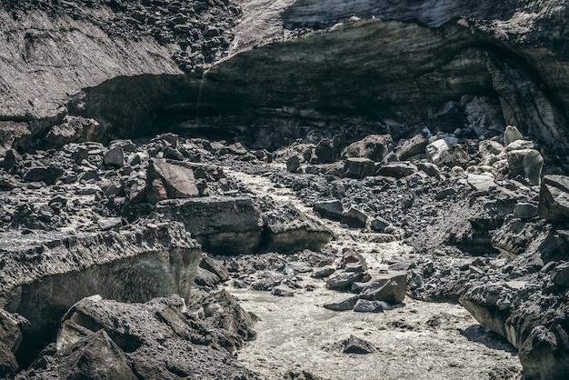 Paesaggio panoramico con fiume di montagna che inizia dal ghiacciaio tra grandi morene. splendido scenario con ghiacciaio alla sorgente del fiume. torrente di montagna dal ghiaccio tra grandi pietre. sorgente del fiume dal ghiacciaio