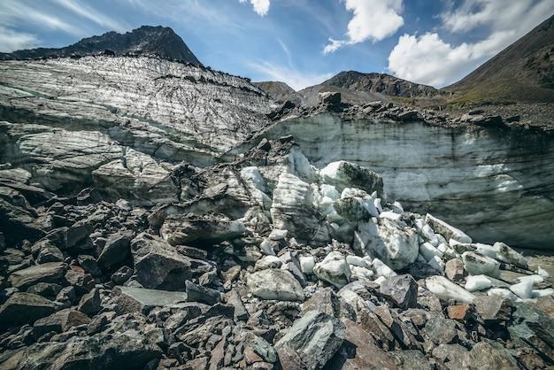 Paesaggio montano panoramico con grande ghiacciaio e alta cima in una giornata di sole. fantastico scenario dell'altopiano con collina ghiacciata con grandi pietre e picco di montagna. ghiaccio del ghiacciaio tra morene. blocchi di ghiaccio alla luce del sole.