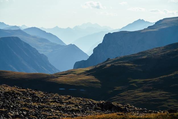 Scenic paesaggio di montagna con montagne rocciose giganti e profonda gola dietro una collina verde alla luce del sole.