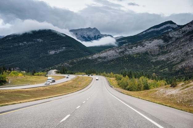 Viaggio stradale scenico con la montagna rocciosa nella foresta di autunno al parco nazionale di banff