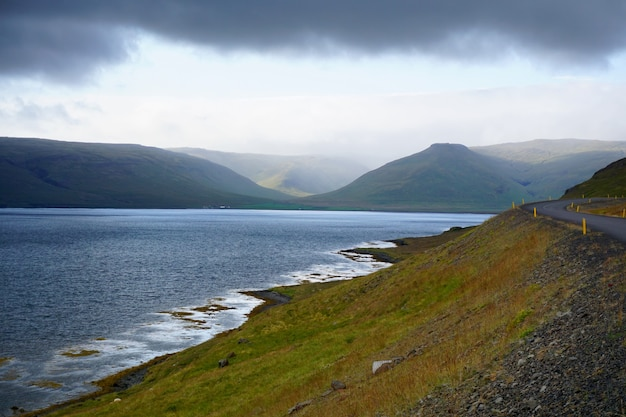Vista panoramica del drammatico paesaggio islandese con strada vuota accanto a un fiordo.