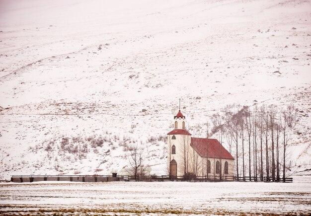 La vista scenica della chiesa sola nell'inverno dopo la bufera di neve in islanda.