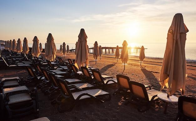 Vista panoramica della spiaggia privata di sabbia sulla spiaggia con lettini contro il mare e le montagne.