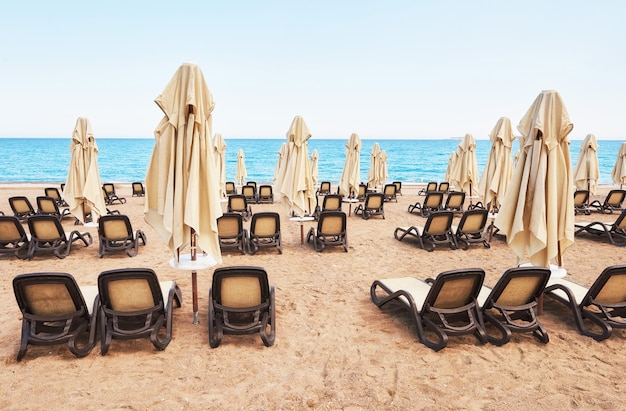 Vista panoramica della spiaggia privata di sabbia con lettini dal mare e dalle montagne.