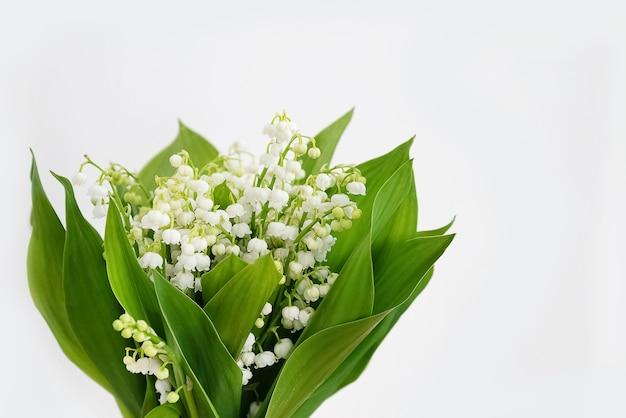 Mazzo profumato di fiori di mughetto sulla superficie della parete bianca