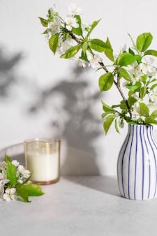 Candela profumata e fiori di ciliegio in vaso sul tavolo