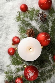 Candela profumata, rami di pino con palline sul tavolo con la neve