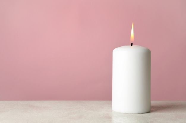 Candela profumata per rilassarsi sul tavolo bianco su sfondo rosa