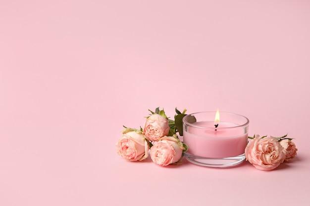 Candela profumata e rose su sfondo rosa