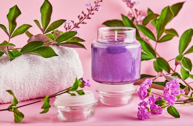 Candela profumata per spa e casa con profumo di lavanda e foglie verdi su uno spazio rosa.