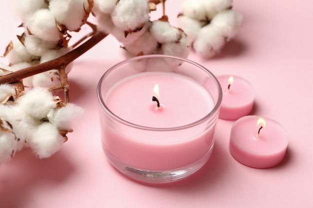 Candele profumate e cotone su sfondo rosa