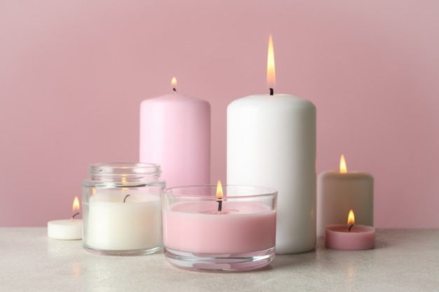Candele profumate per rilassarsi sul tavolo bianco su sfondo rosa