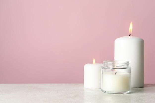 Candele profumate per il relax sul tavolo bianco contro la superficie rosa