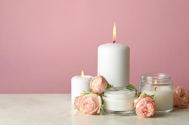 Candele profumate e rose sul tavolo bianco su sfondo rosa