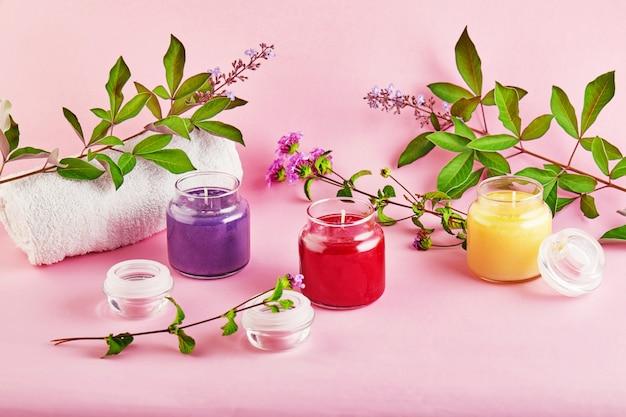 Candele profumate per spa e casa con foglie verdi su uno spazio rosa.