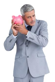 Uomo d'affari scettico che tiene porcellino salvadanaio