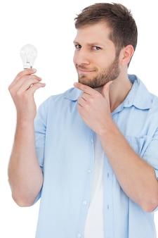 Modello scettico che tiene una lampadina e che guarda l'obbiettivo