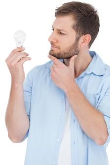 Modello scettico che tiene una lampadina e guardandola